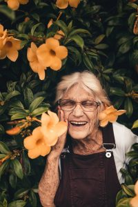 Photo of beautiful elderly woman by flowering tree